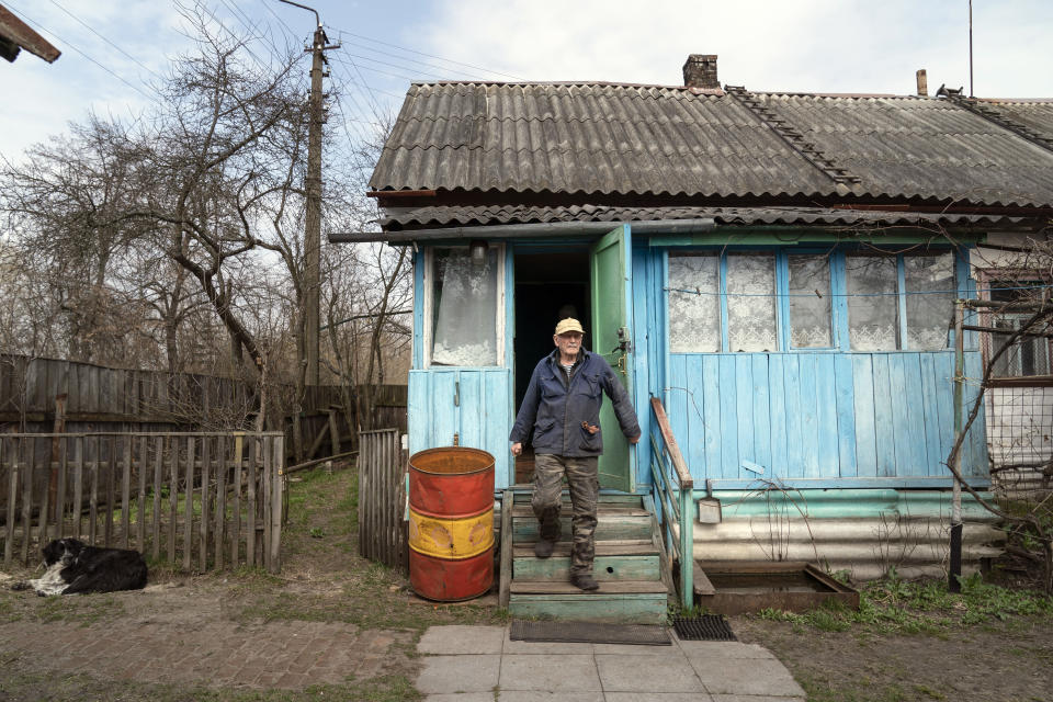 "Yevgeny Markevich, a 85-year-old former teacher, leaves his house at the Chernobyl exclusion zone, Ukraine, Wednesday, April 14, 2021. Markevich said ""It's a great happiness to live at home, but it's sad that it's not as it used to be."" Today, he grows potatoes and cucumbers on his garden plot, which he takes for tests ""in order to partially protect myself."" The vast and empty Chernobyl Exclusion Zone around the site of the world's worst nuclear accident is a baleful monument to human mistakes. Yet 35 years after a power plant reactor exploded, Ukrainians also look to it for inspiration, solace and income. (AP Photo/Evgeniy Maloletka)"