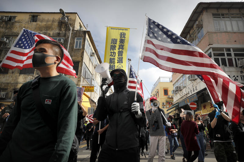 "Protesters carry U.S. flags as they march during a demonstration against ""parallel traders"" who buy goods in Hong Kong to resell in mainland China in Sheung Shui, near the Chinese border in Hong Kong, Sunday, Jan. 5, 2020. Protesters in Hong Kong marched through the border town Sunday to oppose traders from mainland China. (AP Photo/Andy Wong)"