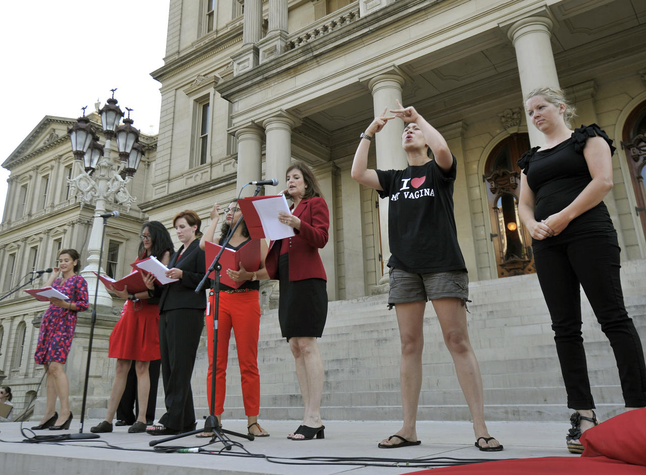 "Rep Lisa Brown, D-West Bloomfield, center, reads her part during a performance of ""The Vagina Monologues"" with 10 other lawmakers and several actresses on the Michigan Statehouse steps, Monday, June 18, 2012, in Lansing, Mich. Brown, who says she was barred from speaking in the Michigan House because Republicans objected to her saying ""vagina"" during debate over anti-abortion legislation, performed ""The Vagina Monologues"" with a hand from the author Eve Ensler. (AP Photo/Detroit News, Dale G. Young)"