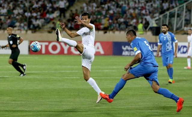 Iran's Masoud Shojaei (L) fights for the ball during a 2018 World Cup qualifying football match between Iran and Uzbekistan in Tehran on June 12, 2017