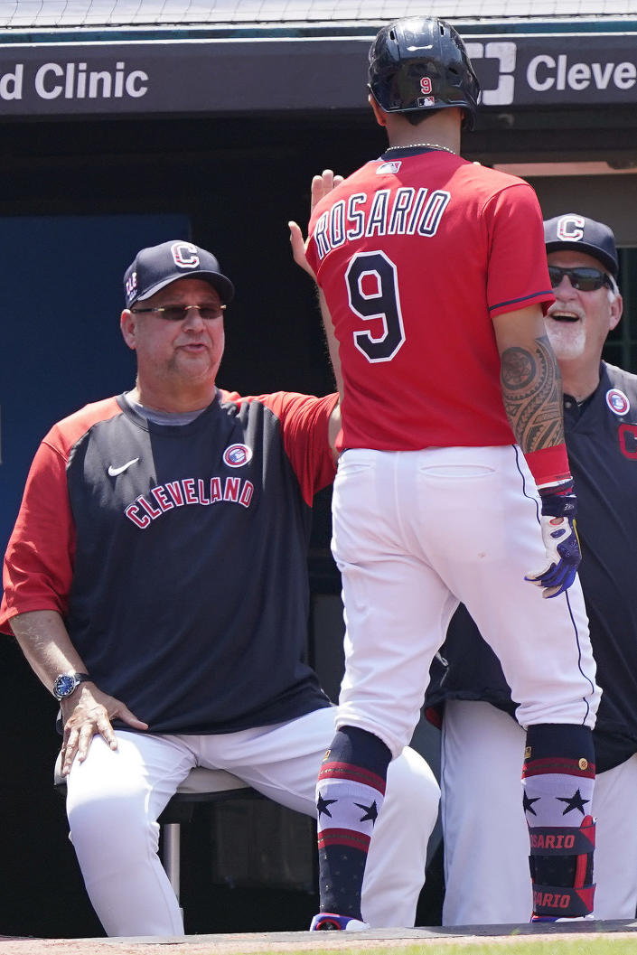 Cleveland Indians' Eddie Rosario, right, is congratulated by manager Terry Francona, left, after hitting a solo home run in the sixth inning of a baseball game against the Houston Astros, Sunday, July 4, 2021, in Cleveland. (AP Photo/Tony Dejak)