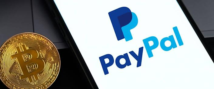 PayPal logo on the screen iPhone with bitcoin cryptocurrency in the dark.