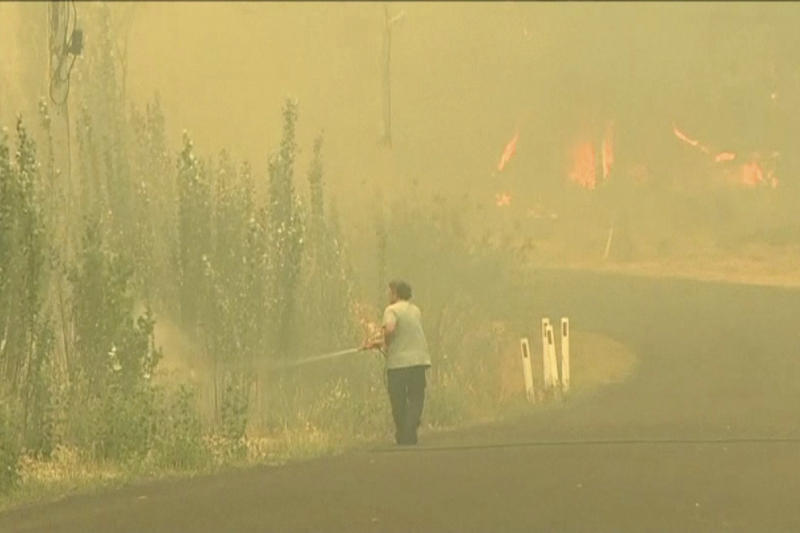 In this image made from video taken Dec. 21, 2019, a man sprays water on a fire in Lithgow, New South Wales state, Australia.  Australian Prime Minister Scott Morrison on Sunday apologized for taking a family vacation in Hawaii as deadly bushfires raged across several states, destroying homes and claiming the lives of two volunteer firefighters.(Australian Broadcasting Corporation via AP)