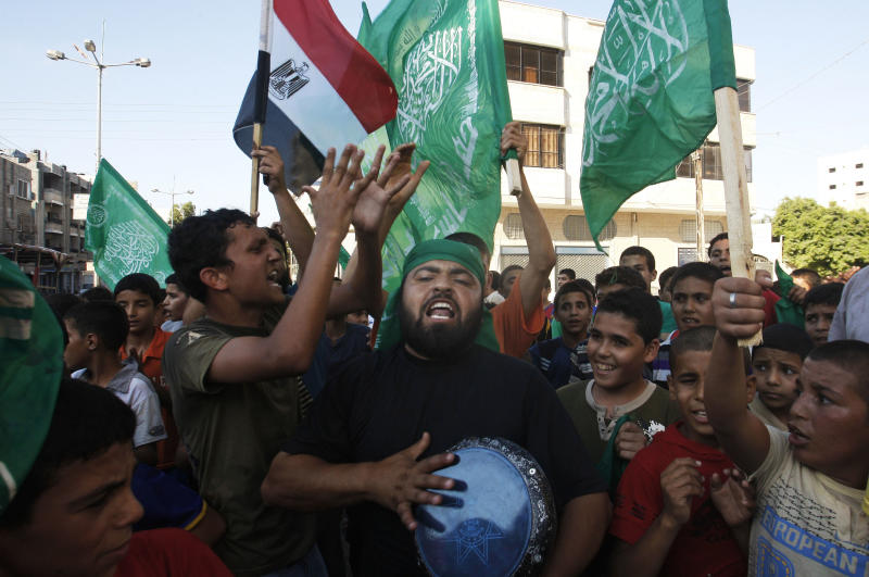 Palestinians wave green Islamic flags that represent Hamas and the Egyptian national flag as they celebrate the victory of Mohammed Morsi in the Egyptian presidential elections, in Gaza City, Sunday, June 24, 2012. The Muslim Brotherhood victory in Egyptian presidential elections raises fears in Israel that the historic 1979 peace agreement with its southern neighbor is now in danger, a scenario that would have grave implications for regional security. But in the Hamas-ruled Gaza Strip, ecstatic residents flock to the streets, fire guns into the air and distribute candies in celebration, hopeful that Mohammed Morsi's election will usher in a new era for the blockaded seaside territory. (AP Photo/Hatem Moussa)