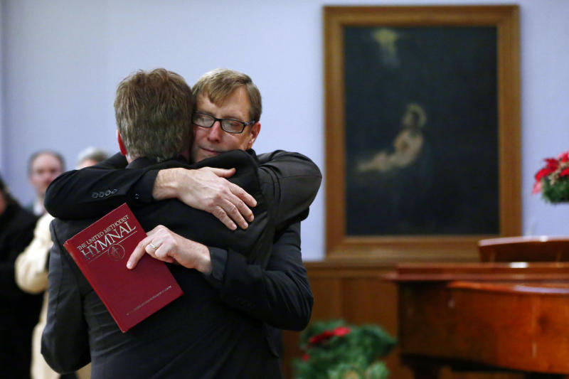 FILE - In this Monday, Dec. 16, 2013 file photo, the Rev. Robin Hynicka, right, embraces the Rev. Frank Schaefer, a United Methodist clergyman convicted of breaking church law for officiating at his son's same-sex wedding, during a news conference at the Arch Street United Methodist Church in Philadelphia. Schaefer plans to defy a church order to surrender his credentials for performing a same-sex wedding. (AP Photo/Matt Rourke)