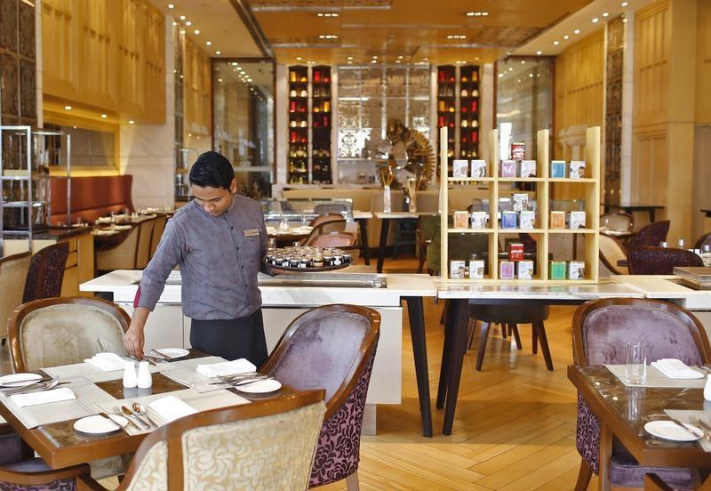 An employee sets a table inside a restaurant at the Crown Plaza hotel, run by IHG, in New Delhi