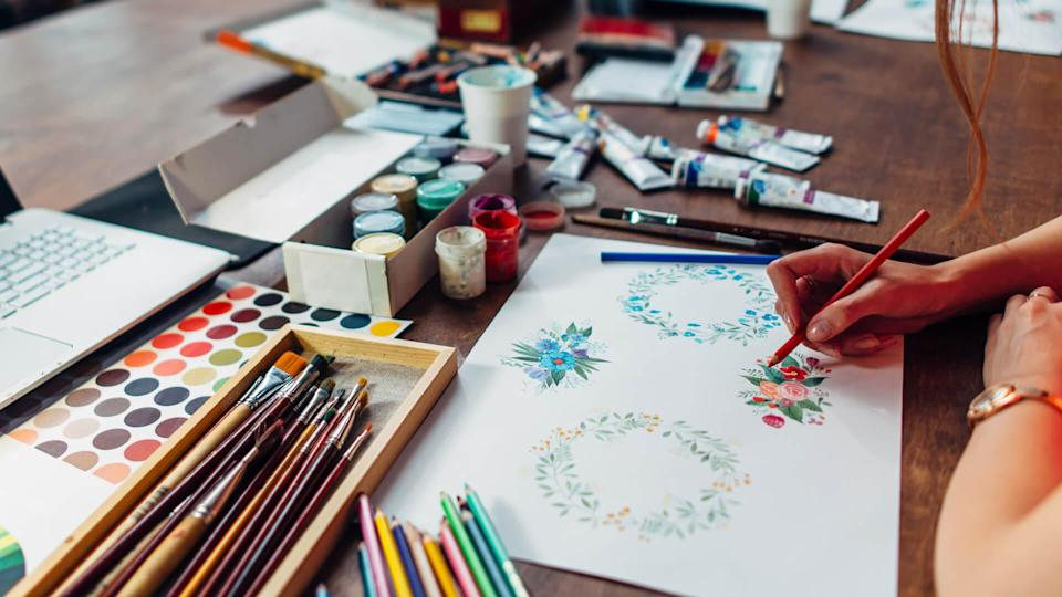 Close-up of female designer drawing floral compositions with crayons sitting at workplace surrounded with paint, gouache, brushes and other art supplies.