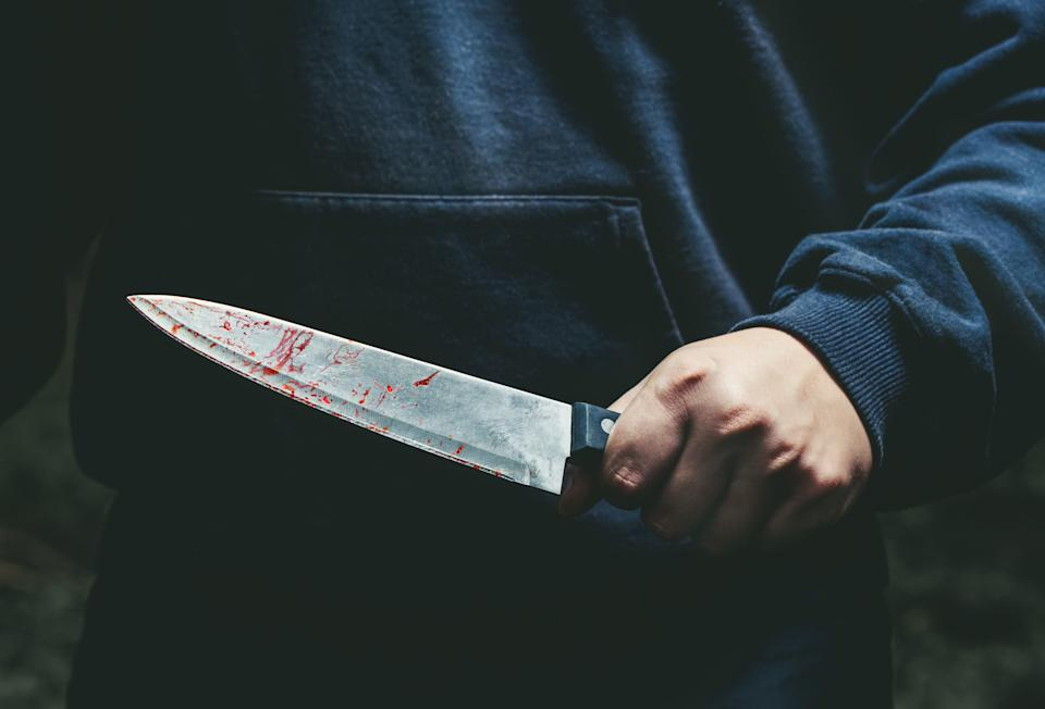 A man with a bloody knife in his hand close up.