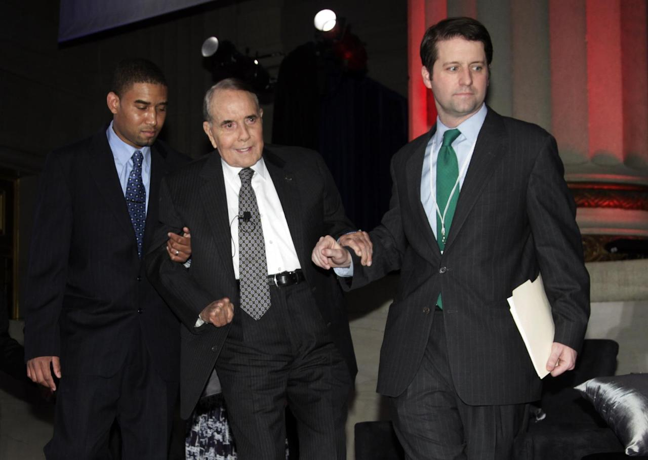 """Former U.S. Senate Majority Leader Bob Dole is helped to his seat during """"A Century of Service"""" honoring former U.S. Senate Majority Leaders Bob Dole and Howard Baker at Mellon Auditorium, Wednesday, March 21, 2012, in Washington. (AP Photo/Carolyn Kaster)"""