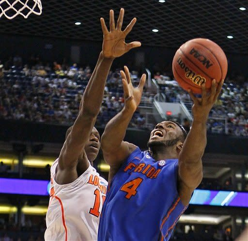 Florida's Patric Young (4) shoots over Louisville defender Gorgui Dieng during the second half of an NCAA tournament West Regional final college basketball game on Saturday, March 24, 2012, in Phoenix. (AP Photo/Matt York)