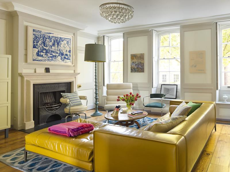 The living room sits level with the leaves of the London plane trees that grow along the street outside and are reputed to have been planted by one of the house's former owners. The B&B Italia sofa has been custom-upholstered in a vibrant mustard yellow and teamed with a cluster of design-classic chairs, including a Cassina LC7, in front of the fireplace.