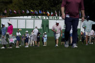 Patrons walk by the main scoreboard during a practice day for the Masters golf tournament on Tuesday, April 6, 2021, in Augusta, Ga. (AP Photo/Gregory Bull)
