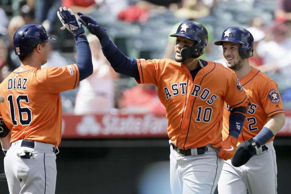 Houston Astros' Yuli Gurriel, center, gets congratulations from Aledmys Diaz, left, after hitting a two-run home run to also score Alex Bregman, right, during the third inning of a baseball game against the Los Angeles Angels in Anaheim, Calif., Sunday, Sept. 29, 2019. (AP Photo/Alex Gallardo)