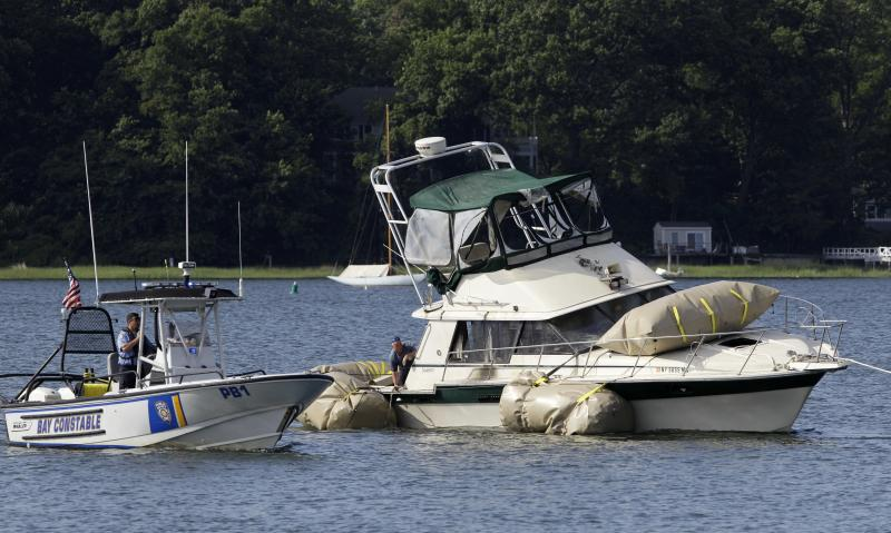 A yacht that capsized and sank off of New York's Long Island is towed after being lifted with airbags from the bottom of a bay in Oyster Bay, N.Y., Wednesday, July 11, 2012. FBI divers and Nassau County police raised the 34-foot Kandi Won from about 60-feet of water in the hopes that inspecting it will provide clues into the cause of a deadly accident that killed three children who were on board when it capsized during an outing to watch a Fourth of July fireworks display. (AP Photo/Kathy Willens)