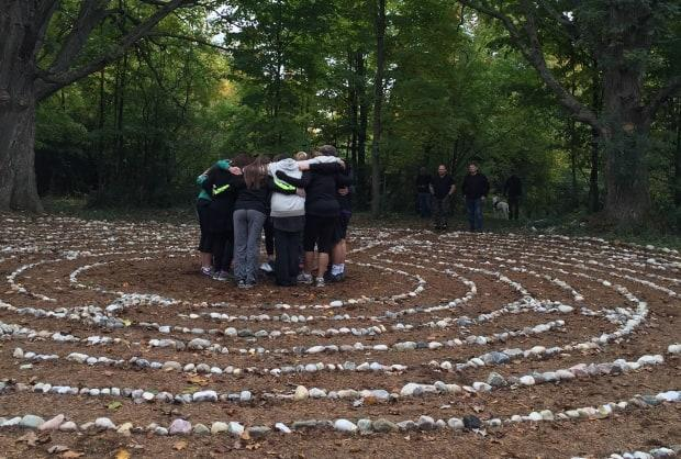 Female participants of Project Trauma Support in Perth, Ont., join in a group hug at the centre of a labyrinth. The charity is not funded by the Canadian Armed Forces.