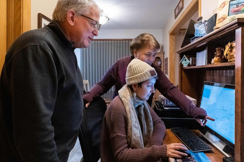 Dan Maccoux, his wife Cathy Maccoux(L) and daughter Olivia Maccoux look at the computer on January 16, 2020 in Brooklyn Park, Minnesota - He may be insured and has a six-figure salary but after spending hundreds of thousands of dollars on care for his daughter Olivia, Dan Maccoux expects to be in debt for the rest of his life -- victim of a ferociously expensive US health system that Donald Trump's challengers for the presidency have pledged to overhaul or scrap. (Photo by Kerem Yucel / AFP) (Photo by KEREM YUCEL/AFP via Getty Images)