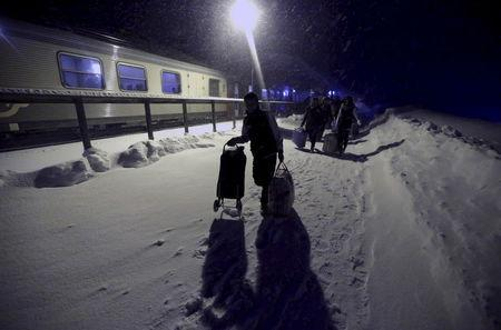 Refugees disembark and make their way to a camp at a hotel touted as the world's most northerly ski resort in Riksgransen, Sweden, in this December 15, 2015 file photo. REUTERS/Ints Kalnins/Files