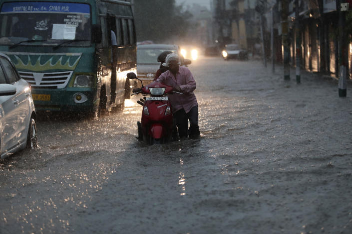A man pushes a two wheeler through a flooded street during monsoon rains Jammu, India, Monday, July 12, 2021. India's monsoon season runs from June to September. (AP Photo/Channi Anand)