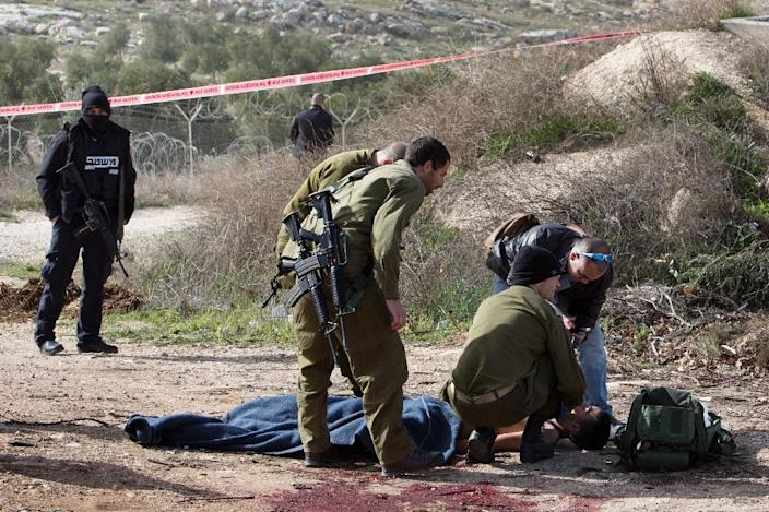 An injured Palestinian suspected attacker is treated by Israeli medic soldiers after he was shot following a stabbing attack on January 18, 2016 in the Tekoa settlement, south of Jerusalem (AFP Photo/Menahem Kahana)