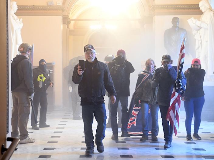 Pro-Donald Trump rioters enter the U.S. Capitol as tear gas fills the corridor on Jan. 6, 2021, in Washington, D.C. Mobs breached security and entered the Capitol as Congress debated the 2020 presidential election.