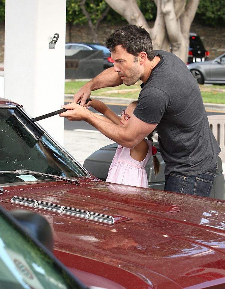 Oscar winner Ben Affleck and his 7-year-old daughter, Violet, had a daddy-daughter moment when he showed her how to help him clean the car windshield as they stopped for gas in L.A. (7/23/2013)