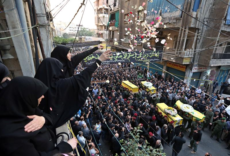 Lebanese woman throw flowers as Hezbollah supporters carry the coffins of four people, including Radwan Fares, a Lebanese national who headed the facility's security, who were killed a day after two suicide bombings struck the Iranian Embassy in Beirut, during their funeral procession, in the southern suburb of Beirut, Lebanon, Wednesday, Nov. 20, 2013. Thousands of people attended the funerals in Ghobeiri, a stronghold of Hezbollah in southern Beirut. At least 23 people were killed and more than 140 were wounded in Tuesday's twin suicide attacks. (AP Photo/Bilal Hussein)