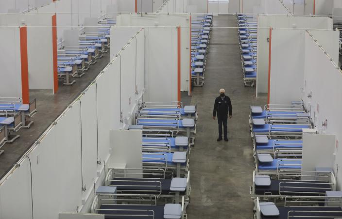 FILE - In this Tuesday, May 26, 2020 file photo a person stands in an aisle of a converted field hospital at the Cape Town International Convention Centre, in Cape Town, South Africa. (AP Photo/Nardus Engelbrecht, File)