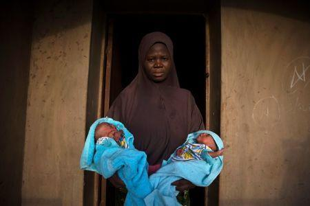 A Muslim woman carries her four-day-old male twins wrapped in blue towels outside the door of her home in Igbo Ora, Oyo State, Nigeria April 3, 2019. PIcture taken April 3, 2019. REUTERS/Afolabi Sotunde