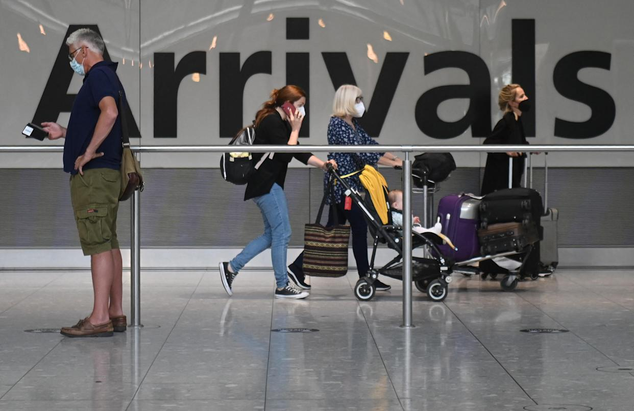 Passengers push their luggage on arrival in Terminal 5 at Heathrow airport in London, on June 3, 2021. - Health Secretary Matt Hancock has said it remains