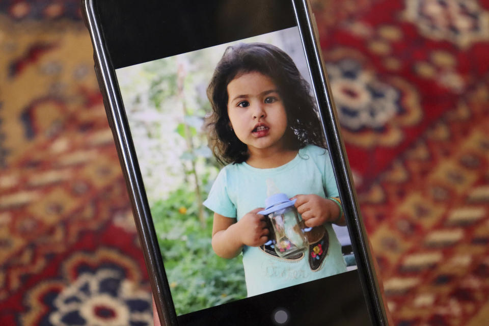 Emal Ahmadi shows a photo of a family member who was killed