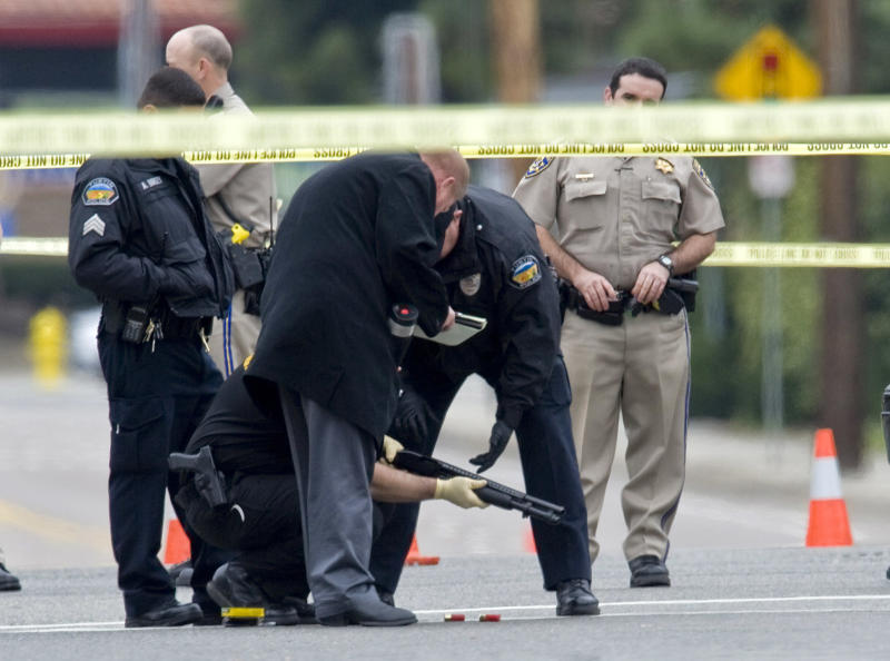 Police investigators examine a gun laying in the street at the intersection of Wanda Road and Katella Avenue in Orange, Calif., early Tuesday, Feb. 19, 2013 near where a body laid moments before. A shooting spree early Tuesday left three people dead and two others injured in Orange County, and the search for the gunman ended when he shot himself to death in a stolen car as police closed in, authorities said.(AP Photo/The Orange County Register, Mark Rightmire) MAGS OUT; LOS ANGELES TIMES OUT