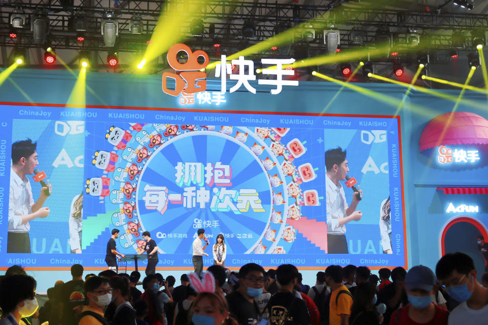 In this July 31, 2020, photo, people watch a performance presented by Chinese technology firm Kuaishou at the ChinaJoy expo in Shanghai. China's internet watchdog has fined technology platforms operated by e-commerce company Alibaba and gaming firm Tencent for spreading sexually suggestive content involving children, as regulators sought to clean up the internet of content harmful to minors. (Chinatopix via AP)