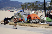 FILE - In this June 8, 2021, file photo, a jogger runs past a homeless encampment in the Venice Beach section of Los Angeles. California has built 6,000 new housing units statewide over the last year as part of Project Homekey, launched at the height of the pandemic to re-purpose vacant hotels, motels and other unused property as permanent supportive housing for the homeless, the lynchpin of Gov. Gavin Newsom's $12 billion plan to combat homelessness. (AP Photo/Marcio Jose Sanchez, File)