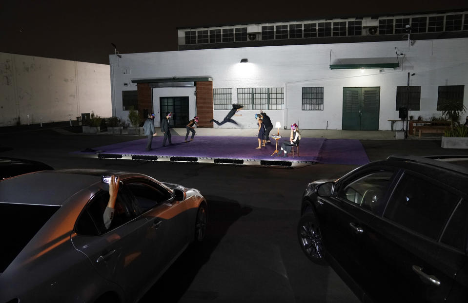 """Audience members in their cars watch """"Solo at Dusk,"""" a work by Bobbi Jene Smith in collaboration with Or Schraiber, during the opening night of L.A. Dance Project's Drive-In Dances series, Thursday, Sept. 10, 2020, in downtown Los Angeles. The series was conceived by L.A. Dance Project to safely bring live dance back to Los Angeles during the COVID-19 era by reimagining their 2020-2021 season as a drive-in experience. (AP Photo/Chris Pizzello)"""
