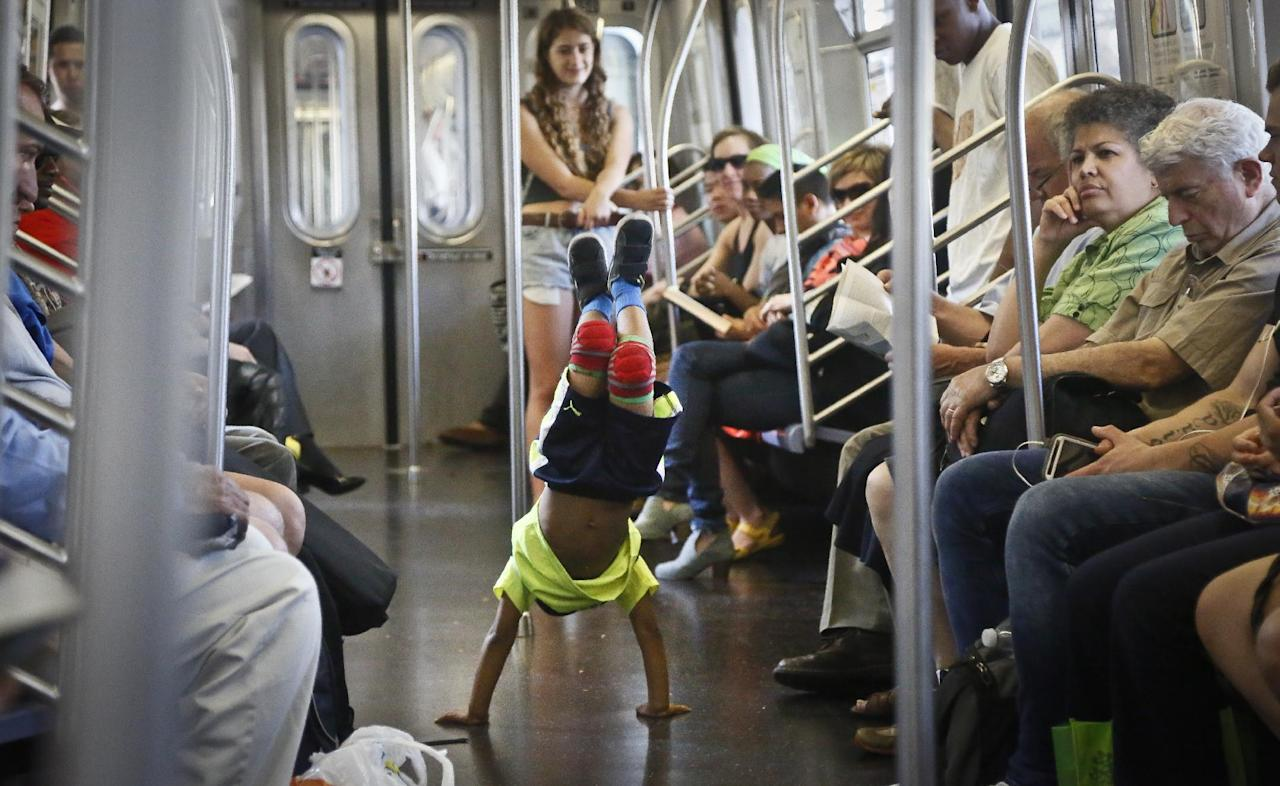 In this June 17, 2014 photo, acrobatic dancer Nasir Malave, 5, dances on a subway train in New York. The New York Police Department is cracking down on the subway showmen who use the tight quarters of the nation's busiest transit system as moving stages for impromptu, and illegal, pass-the-hat performances. (AP Photo/Bebeto Matthews)