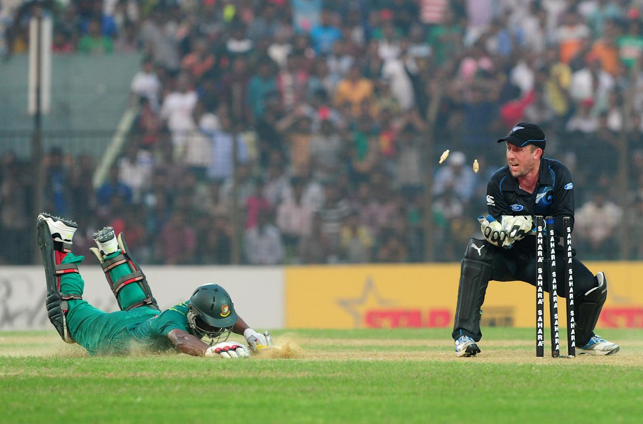 New Zealand wicketkeeper Luke Ronchi stumps Bangladesh batsman Naeem Islam (L) is run out by New Zealand wicketkeeper Luke Ronchi during the third One-Day International (ODI) cricket match between Bangladesh and New Zealand at Khan Jahan Ali Stadium in Fatullah on the outskirts of Dhaka on November 3, 2013. AFP PHOTO/ Munir uz ZAMAN        (Photo credit should read MUNIR UZ ZAMAN/AFP/Getty Images)