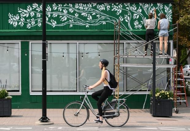 A cyclist rides past as Tori Lubbers and Emily Beckman, top right, paint a mural above the windows of the Green Door Restaurant in Ottawa, on Tuesday, Aug. 3, 2021.  (Justin Tang/The Canadian Press - image credit)