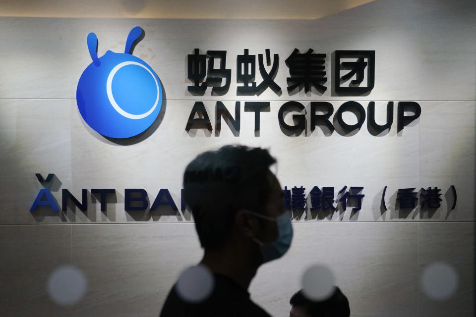 In this Friday, Oct. 23, 2020, photo, an employee walks past a logo of the Ant Group at their office in Hong Kong. The world's largest fintech company, China's Ant Group, will try to raise nearly $35 billion in a massive public offering of stock that would shatter records. (AP Photo/Kin Cheung)