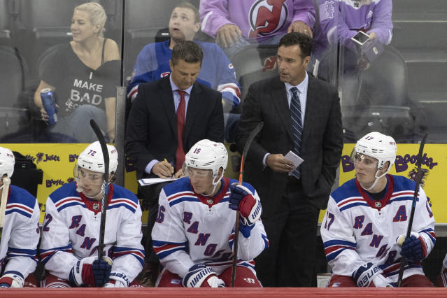 New York Rangers coach David Quinn watches the team play the New Jersey Devils during the third period of a preseason NHL hockey game, Friday, Sept. 20, 2019, in Newark, N.J. (AP Photo/Mary Altaffer)