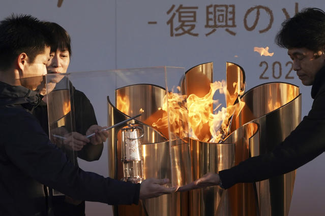 """Officials light a lantern from the Olympic Flame at the end of a flame display ceremony in Iwaki, northern Japan, Wednesday, March 25, 2020. IOC President Thomas Bach has agreed """"100%"""" to a proposal of postponing the Tokyo Olympics for about one year until 2021 because of the coronavirus outbreak. (AP Photo/Eugene Hoshiko)"""