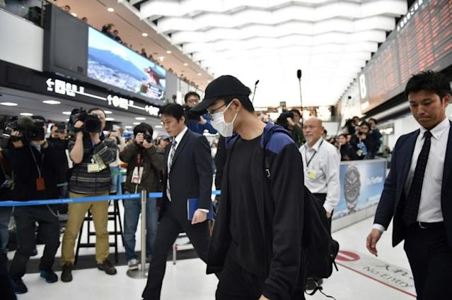 Badminton world number one Kento Momota arrived in Japan wearing a face mask after sustaining injuries in a road accident (AFP Photo/Kazuhiro NOGI)
