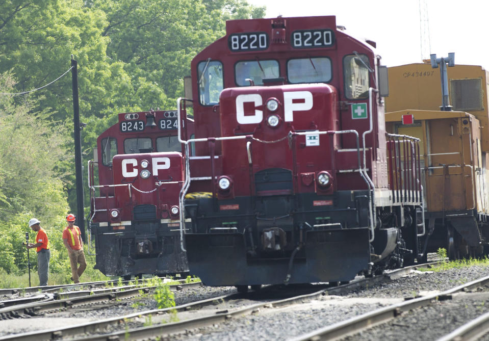FILE - In this May 23, 2012, file photo, surveyors work next to Canadian Pacific Rail trains which are parked on the train tracks in Toronto. A planned shareholder vote on Canadian National's $33.6 billion offer has been delayed, Wednesday, Sept. 1, 2021, after regulators rejected a key part of the plan, so now Kansas City Southern can consider all of its options, including a competing $31 billion offer from Canadian Pacific Railway. (Nathan Denette/The Canadian Press via AP, File)