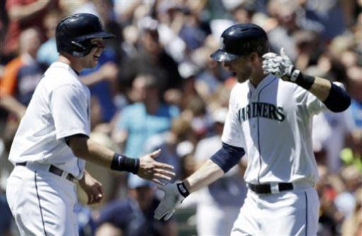 Seattle Mariners' Michael Saunders, right, is congratulated on his two-run home run against the Los Angeles Angels by teammate Justin Smoak in the second inning of a baseball game on Sunday, July 14, 2013, in Seattle. (AP Photo/Elaine Thompson)