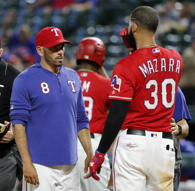 Texas Rangers manager Chris Woodward (8) checks on Nomar Mazara (30), who was hit by a pitch thrown by Cleveland Indians' Adam Cimber in the ninth inning of a baseball game in Arlington, Texas, Wednesday, June 19, 2019. The ball initially hit Mazara on the hip, then ricocheted and also hit him on the face. Mazara remained in the game. (AP Photo/Tony Gutierrez)