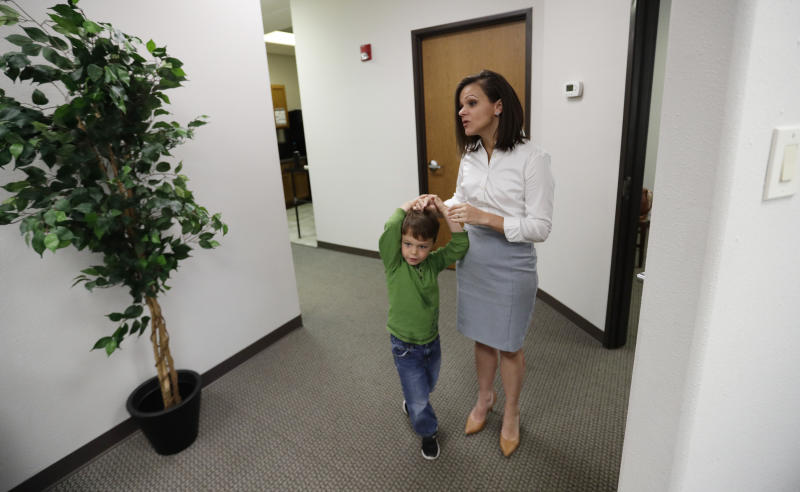 Bethany Babcock, co-owner of Foresite Commercial Real Estate, right, stands with her son, Ethan, at her office in San Antonio, Tuesday, July 23, 2019.  For many small business owners, being a boss means helping staffers when they struggle Babcock, who runs a family friendly business, has bought a plane ticket for a staffer who needed to visit a relative on life support and paid moving expenses for a staffer who was having family problems, as well as permitting staff to bring their children to work.(AP Photo/Eric Gay)