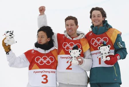 Snowboarding - Pyeongchang 2018 Winter Olympics - Men's Halfpipe Finals - Phoenix Snow Park – Pyeongchang, South Korea - February 14, 2018 - Gold medallist Shaun White of the U.S. is flanked by silver medallist Ayumu Hirano of Japan and bronze medallist Scotty James of Australia as they hold Soohorang Olympic mascots during the flower ceremony. REUTERS/Issei Kato