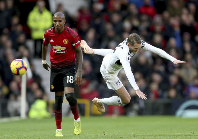 Manchester United's Ashley Young, left and Fulham's Andre Schurrle battle for the ball during the English Premier League soccer match between Manchester United and Fulham, at Old Trafford, Manchester, England, Saturday, Dec. 8, 2018. (Barrington Coombs/PA via AP)