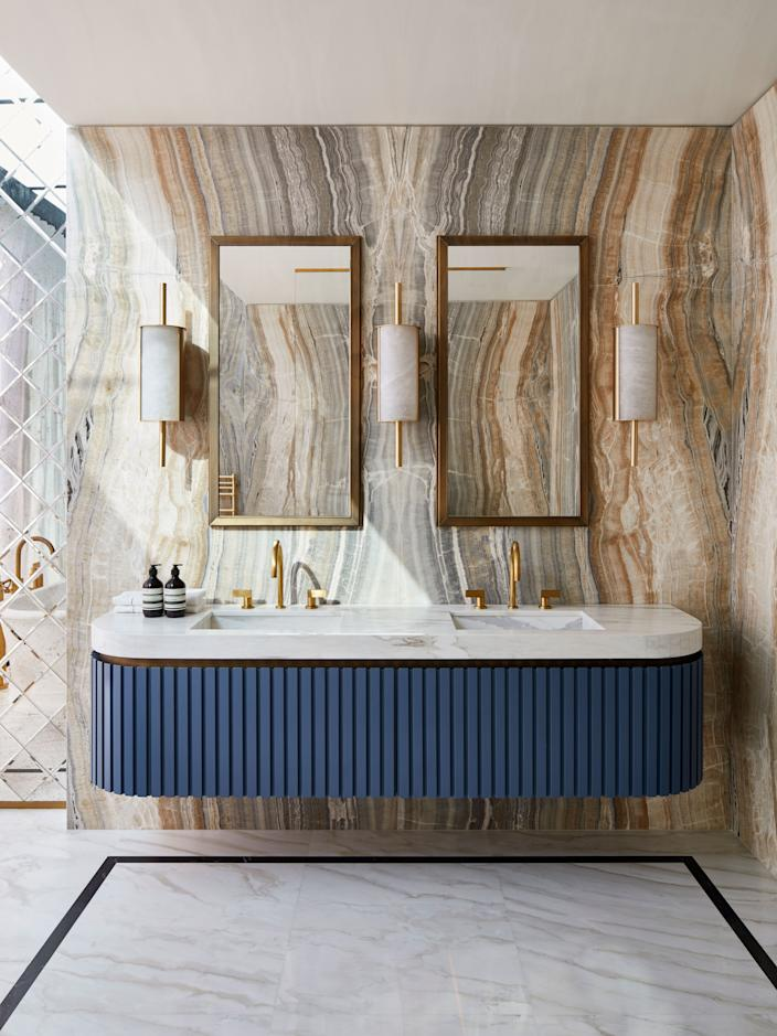 "<div class=""caption""> Custom notched wood vanity in French blue with marble and brass and sinks. Taps in polished brass are <a href=""https://www.volevatch.fr/?lang=en"" rel=""nofollow noopener"" target=""_blank"" data-ylk=""slk:Volevatch"" class=""link rapid-noclick-resp"">Volevatch</a>. Sconces and mirrors by Humbert & Poyet; the walls are onyx. </div>"
