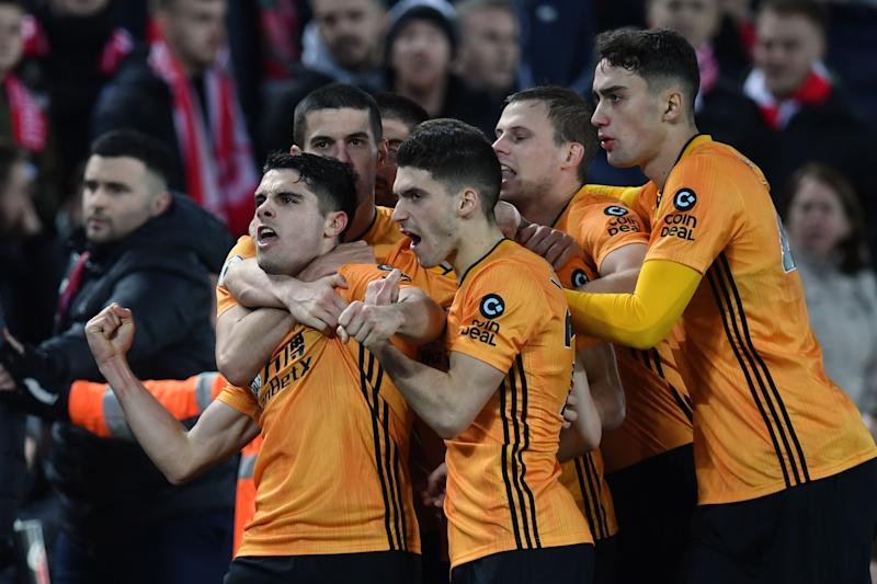 Wolverhampton Wanderers' Portuguese midfielder Pedro Neto (L) celebrates with team-mates after putting the ball in the Liverpool net, a goal that was subsequently ruled out by VAR due to an offside in the build up to it during the English Premier League football match between Liverpool and Wolverhampton Wanderers at Anfield in Liverpool, north west England, on December 29, 2019. (Photo by Paul ELLIS / AFP) / RESTRICTED TO EDITORIAL USE. No use with unauthorized audio, video, data, fixture lists, club/league logos or 'live' services. Online in-match use limited to 120 images. An additional 40 images may be used in extra time. No video emulation. Social media in-match use limited to 120 images. An additional 40 images may be used in extra time. No use in betting publications, games or single club/league/player publications. / (Photo by PAUL ELLIS/AFP via Getty Images)