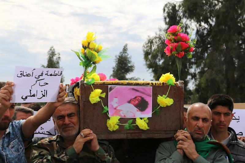 An Iraqi carries the coffin of his three-year-old daughter, killed following a chemical attack by the Islamic State group in the town of Taza, south of Kirkuk, during her funeral on March 11, 2016